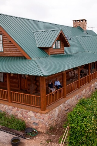 Green R Panel Metal Roof On Log Cabin