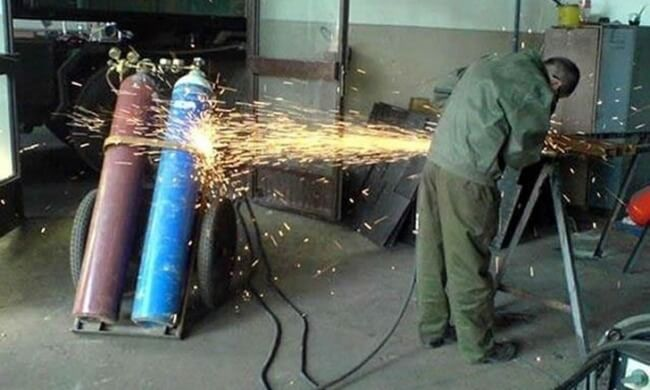 Torch cutting metal with flames bouncing off gas tanks